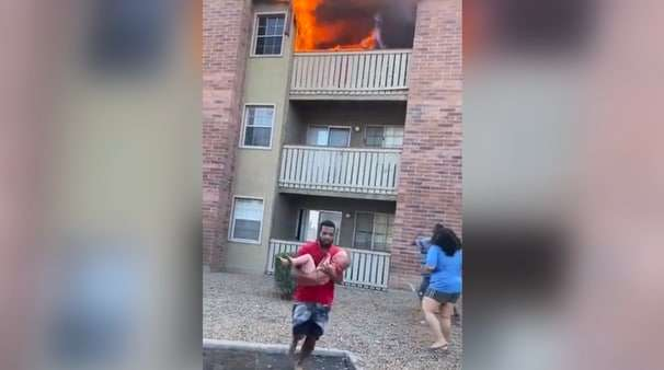 A former high school football player dove and caught a child dropped from the balcony of a burning building