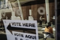 Image: A voter wearing a protective mask carries a ballot at a polling site in Brooklyn on June 23.