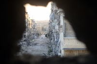 Image: Through a smashed wall, a view of a devastated street in the Salaheddine district of the Syrian city of Aleppo on Aug. 22, 2013.