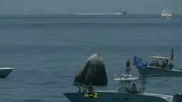 Private boats, one with a Trump flag, pass by SpaceX's capsule recovery site